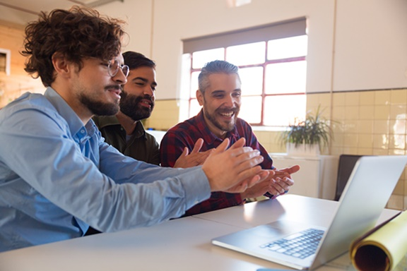 Group of coworkers watching online training or webinar on laptop, applauding speaker. Business colleagues in casual meeting in contemporary office space. Online training concept
